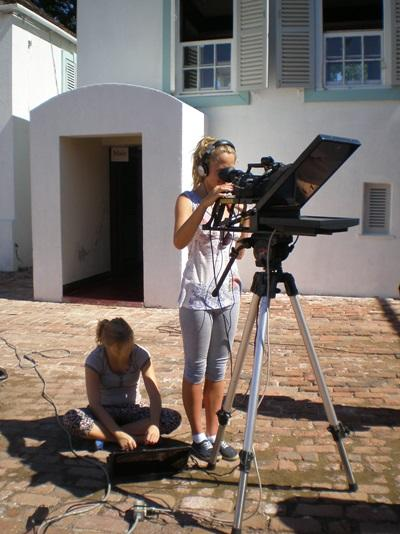 Journalists volunteering in Jamaica record a TV broadcast for a university station.