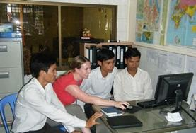 A professional volunteer journalist in Cambodia explains her story to staff in the office.