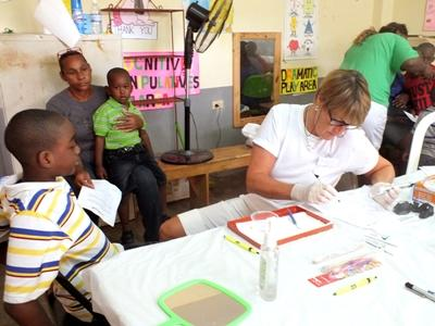 A dentist volunteering in Jamaica works with children at a dental outreach.