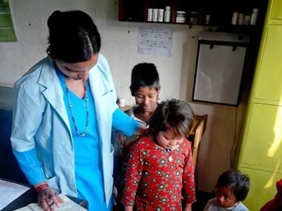 A nurse runs basic health checks for children at a care centre in Nepal.