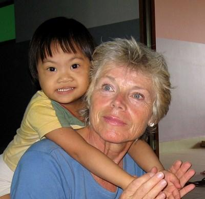 Professional volunteer working with child on occupational therapy project in Cambodia