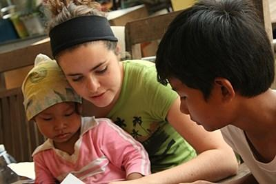 An occupational therapist volunteering in Cambodia works with a group of children at a school.
