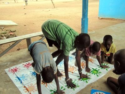 Children do a painting activity with an occupational therapist volunteering in Ghana.