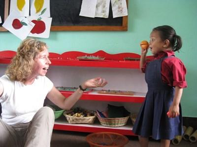 A professional occupational therapist volunteering in Nepal plays with a child at a local school.