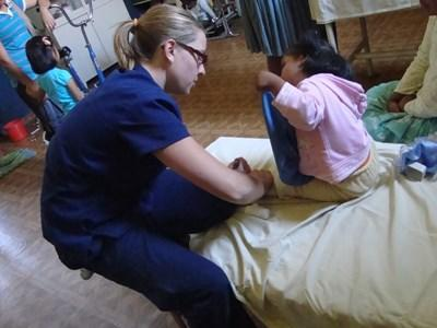 A professional physiotherapist volunteering in Bolivia works with a child at a hospital.