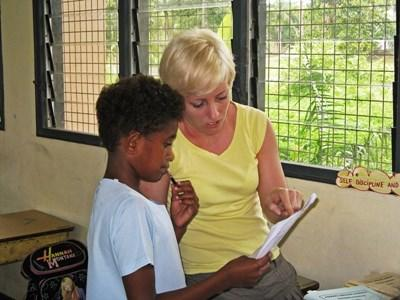 A speech therapist works with a child at a school during her time volunteering in Fiji.