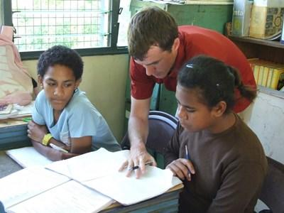 A speech therapist volunteering in Fiji works with children who have speech difficulties.