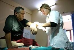 A professional volunteer acupuncturist assists a man in a hospital based in Nepal.