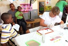 A professional dentistry volunteer assists young children in Jamaica on the Professional Dental Project.