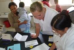 A professional dietitian volunteer in Bolivia assists a local woman and her child during her project work.