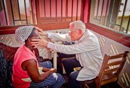 A volunteer doctor examines a local woman in Ghana as part of his project for professionals.