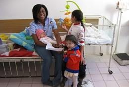 A qualified professional massage therapy volunteer works with young children at a care centre in Romania.