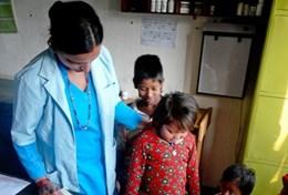 A professional volunteer nurse helps weigh children in Nepal as part of her project work.