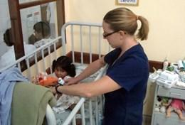 A professional volunteer occupational therapist works with a young girl in Bolivia.