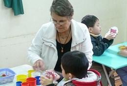 Based in Vietnam, a professional occupational therapy volunteer assists a young child during a therapy session.