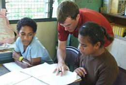 A speech therapist volunteering in Fiji works with school children.