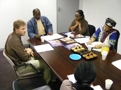 Professional volunteers hold a meeting with local entrepeneurs to discuss business strategyin Tanzania.