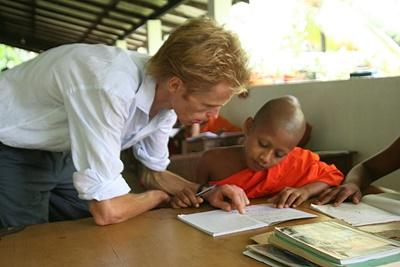 A qualified teacher volunteering in Sri Lanka explains an exercise to a young student.