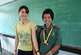A professional teacher volunteering in Thailand with her students in a classroom.