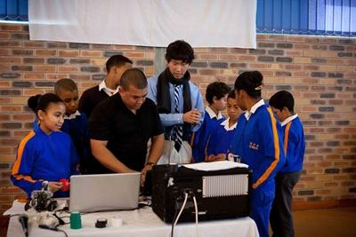 Professional teaching volunteer with students in IT class in South Africa