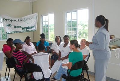 A group of local people attend a community literacy class taught by a professional teacher in Jamaica.