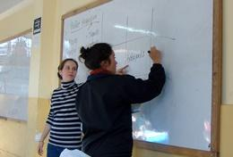 A professional teacher volunteering in Peru helps a student solve a math problem during class.