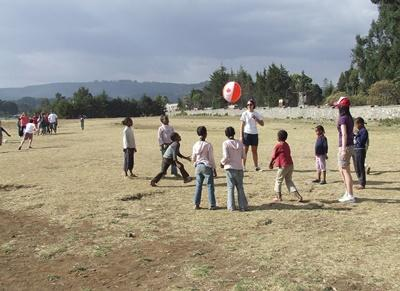 A PE teacher volunteering in Ethiopia runs an exercise class for children at a local school.