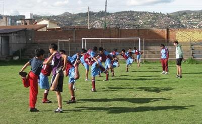 A PE teacher volunteering in Peru runs drills before playing a soccer game.