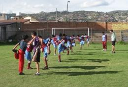 A professional PE teacher volunteering in Peru leads children through soccer drills during class.