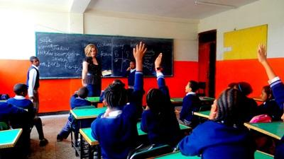 Children raise their hands in class to answer a question asked by a teacher volunteering in Ethiopia.