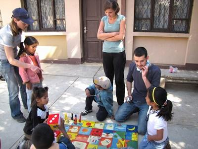 Volunteers run an activity outdoors with children in Bolivia.
