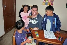 A professional special needs teacher volunteering in Bolivia helps children with an educational activity.