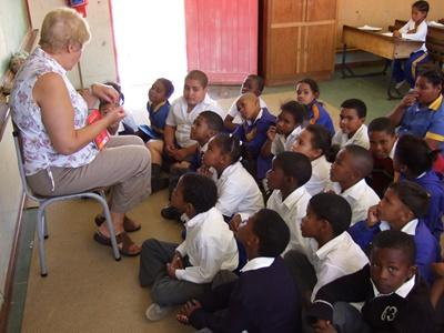Older volunteer teaches young children in a school in South Africa on the Professional Teaching project
