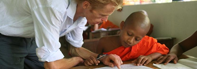 A professional teacher works in a classroom with children abroad.