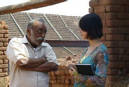 A professional journalist volunteering abroad speaks to a local man for her story.