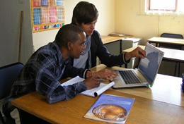 A volunteering businessman assists a local with his business plan.