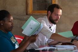 A professional business consultant volunteering abroad helps entrepreneurs develop business plans.