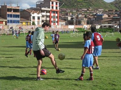 A child watches a Projects Abroad volunteer kick a ball at a soccer practice session in Peru.