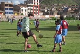 A child practices soccer drills with the help of a volunteer after school sports coach in Peru.