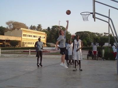Volunteer basketball coach dunks a ball during practice at a school in Ghana.
