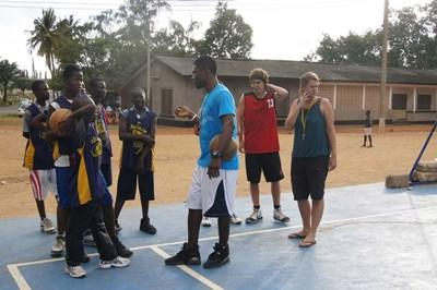 A volunteer coaches basketball to teenagers at a club in Ghana.