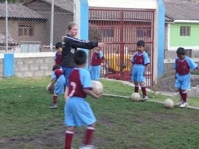 Volunteer soccer coach instructs children at a school in Peru