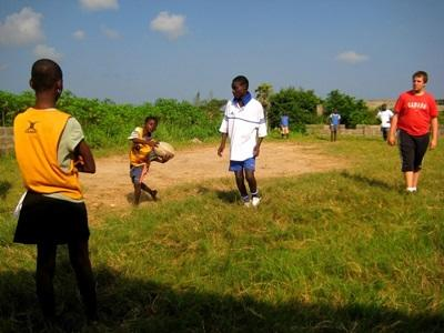 A volunteer coaches rugby to a school team in a developing country abroad.