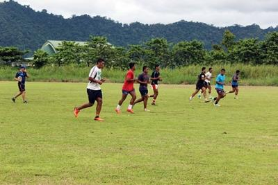 A volunteer rugby coach works with local children to develop their fitness in Samoa.