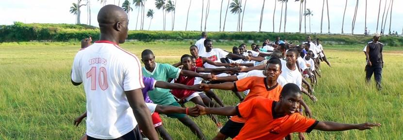 A rugby coach volunteering in a developing country abroad runs a training session.
