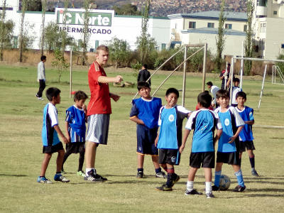 A Projects Abroad volunteer coaches soccer to a group of young children in Bolivia.