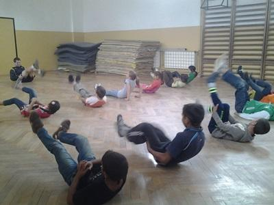 Romanian children participate in warm-up exercises with a volunteer