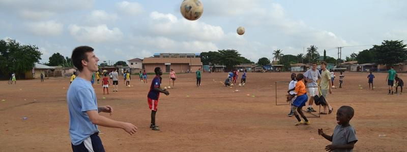 A Projects Abroad volunteer helps a child develop his soccer skills in a developing country abroad.