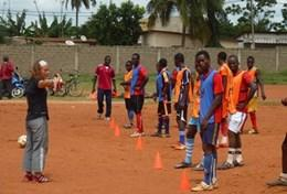 A local team in Togo practices soccer drills while being coached by a sports volunteer.