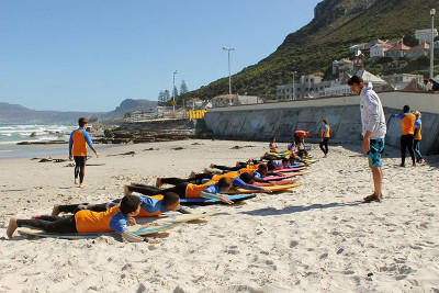 A group of children better their surfing skills during a surfing lesson at Muizenberg beach
